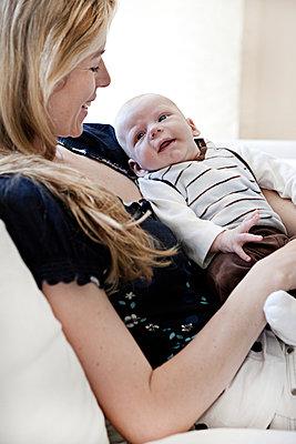 Mutter mit Säugling auf Sofa - p1230m1044548 von tommenz