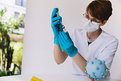 Doctor preparing injection with Corona virus vaccine - p300m2180955 by Mareen Fischinger