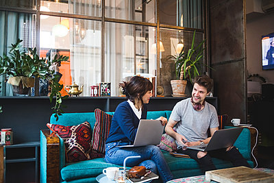 Smiling multi-ethnic female and male professionals discussing over laptop on sofa at office - p426m2089000 by Maskot