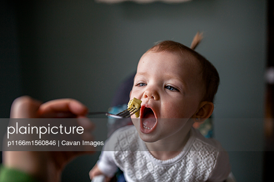 Cropped hand of mother feeding food to daughter with fork at home - p1166m1560846 by Cavan Images