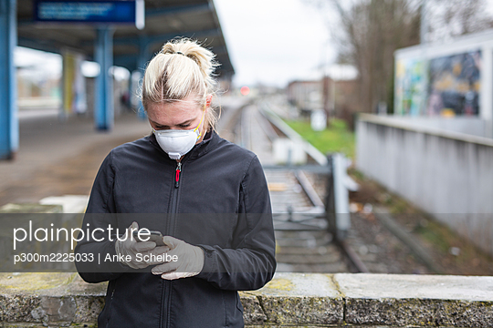 Teenage girl wearing protective mask and gloves using cell phone while waiting at train station - p300m2225033 by Anke Scheibe
