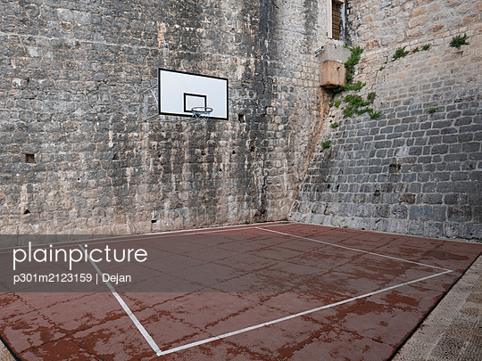 Basketball court and hoop in stone courtyard - p301m2123159 by Dejan