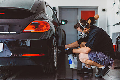 Side view of workers cleaning car in workshop - p1166m2060363 by Cavan Images