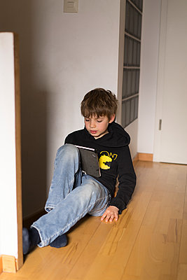 Boy wit tablet PC on the floor, stay at home due to Covid-19 - p1498m2183725 by Nina King