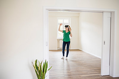 Woman in empty apartment wearing VR glasses - p300m1459983 by Uwe Umstätter