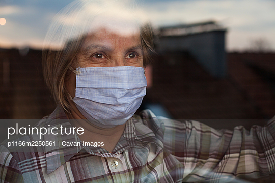 Elderly caucasian woman wearing handmade protective face mask - p1166m2250561 by Cavan Images