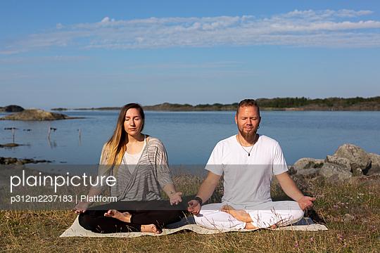 Man and woman meditating at sea - p312m2237183 by Plattform