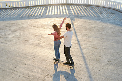 Young couple having fun with longboard - p1124m1503647 by Willing-Holtz