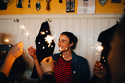 Smiling young woman holding burning sparkler while enjoying with multi-ethnic friends in restaurant during dinner party - p426m2046305 by Maskot