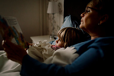 Senior woman reading story book for grandson on bed at home - p426m2195189 by Maskot