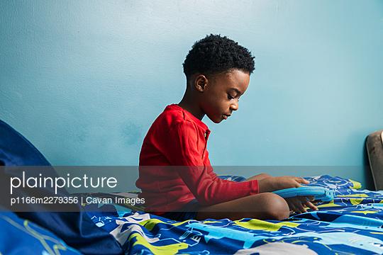 Boy using digital tablet on his bed - p1166m2279356 by Cavan Images