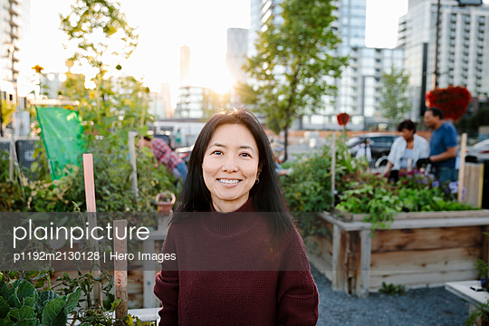 Portrait happy woman in urban community garden - p1192m2130128 by Hero Images