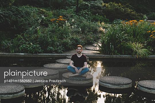 Mann sitzt im Schneidersitz an Wasser - p1491m1582682 von Jessica Prautzsch