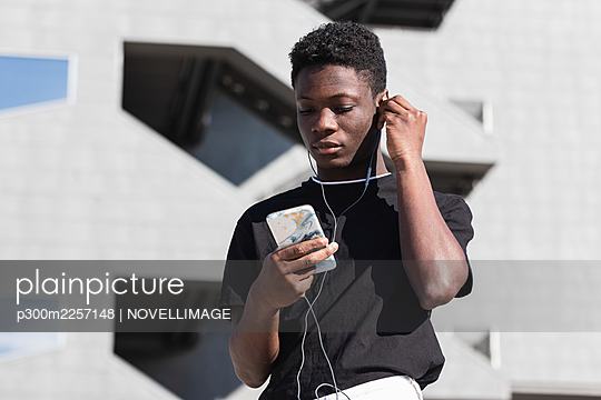 Young man using smart phone while listening music during sunny day - p300m2257148 by NOVELLIMAGE