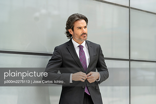 Serious businessman looking away while wearing suit against wall - p300m2275113 by Jose Carlos Ichiro
