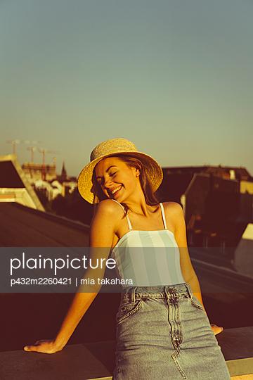Junge Frau mit Hut entspannt auf Hausdach - p432m2260421 von mia takahara