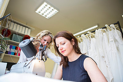 Women working at sewing machine in bridal shop - p1026m1164203 by Patrick Frost