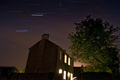 Long Exposure of country farm house at night with stars forming tracers in the sky - p1072m828816 by Brian Korteling
