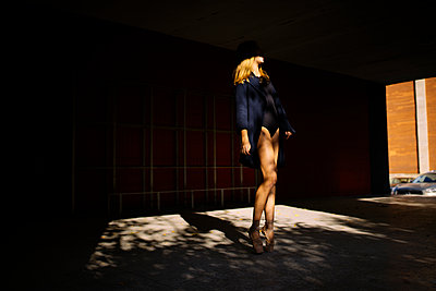 Woman ballerina standing in the shade on the street - p1166m2094207 by Cavan Images