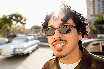 Portrait smiling, confident Latinx man in sunny parking lot - p1192m2062365 by Hero Images