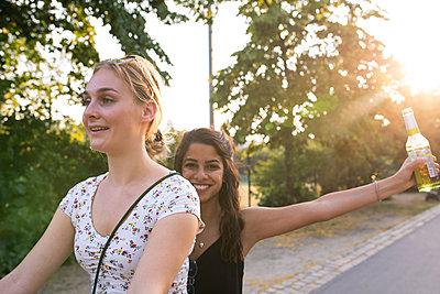 Girlfriends on a bike in a park  - p276m2125568 by plainpicture