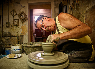 Potter in workshop working on vase - p300m1191890 by Dirk Kittelberger