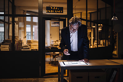 Senior businessman looking at shining tablet in office - p300m2156034 by Gustafsson