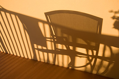 Shadow of chairs and a table on the wall of a tourist resort - p442m2154299 by Mark Hunt