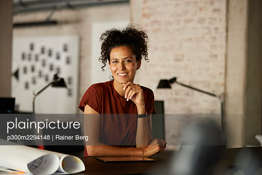 Female professional with hand on chin leaning at workplace - p300m2294148 by Rainer Berg