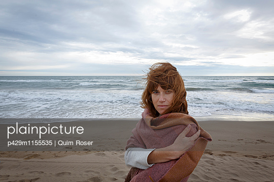 Woman on beach wrapped in blanket looking at camera - p429m1155535 by Quim Roser
