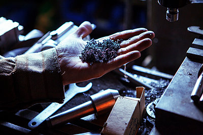 Cropped image of worker holding swarf in workshop - p1166m1209432 by Cavan Images
