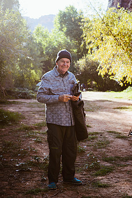 Portrait of smiling man standing on field in forest - p1166m1209541 by Cavan Images