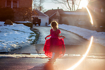 A graceful little girl holds up her long dress and walks on street - p1166m2095917 by Cavan Images
