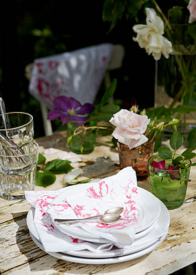 Plate with napkins on English country garden table - p349m789635 by Brent Darby