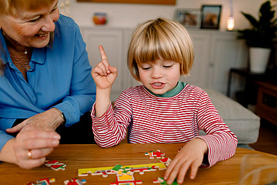 Boy playing jigsaw puzzle with grandmother at home - p426m2195103 by Maskot