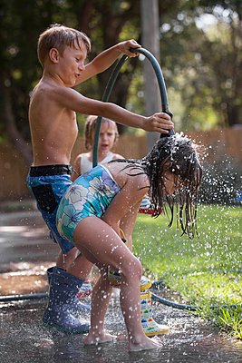 Children playing with water hose on sidewalk - p924m1125756f by Kinzie Riehm