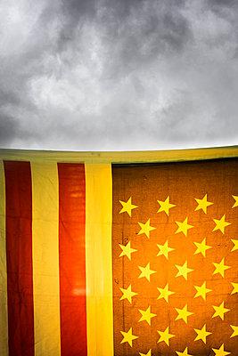 American flag against dark clouds - p975m2286087 by Hayden Verry