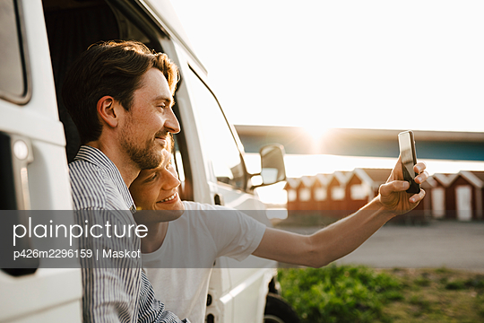 Man taking selfie with boyfriend over smart phone during vacation - p426m2296159 by Maskot
