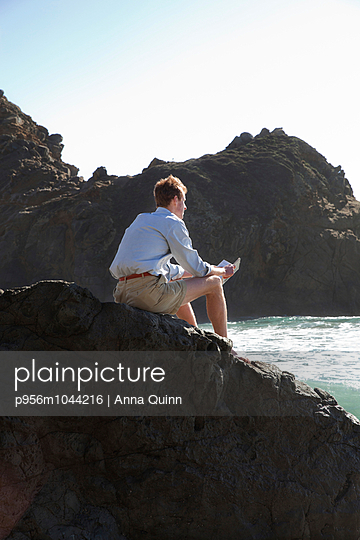 Young man reading on cliff, reading - p956m1044216 by Anna Quinn