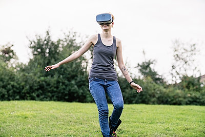 Smiling young woman using Virtual Reality Glasses outdoors - p300m1205487 by A. Tamboly