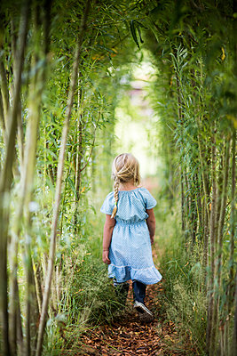 Girl walking in bamboo grove - p312m1229060 by Peter Rutherhagen