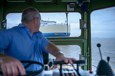 Tugboat towing ship to harbor - p429m747075f by Monty Rakusen