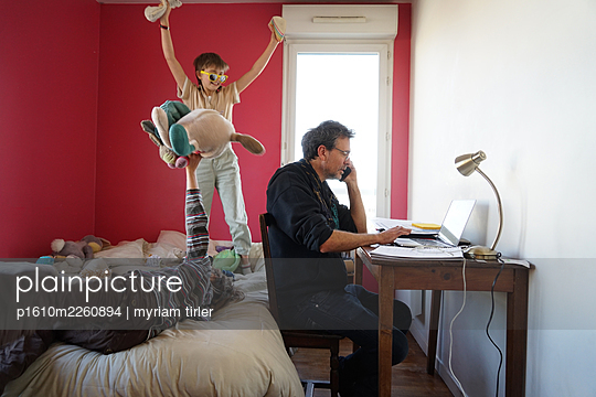 A man working at home with kids playing around - p1610m2260894 by myriam tirler
