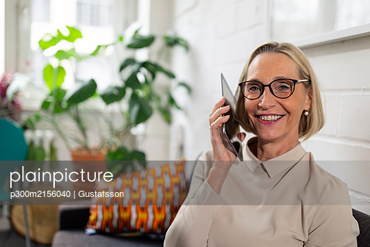 Smiling mature businesswoman using tablet in office lounge - p300m2156040 by Gustafsson