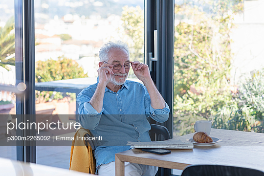 Senior man removing adjusting eyeglasses while sitting by table at home - p300m2265092 by Emma Innocenti