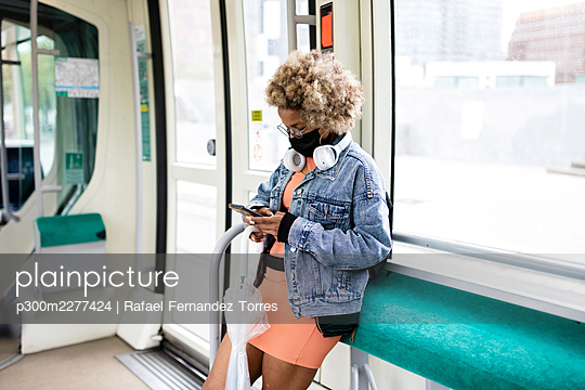 Woman wearing mask using smart phone while traveling in tram during COVID-19 - p300m2277424 by Rafael Fernandez Torres
