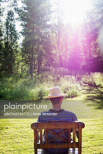 Man With Hat Relaxing On Chair In Garden, Sweden   - p847m2104772 by Anna Molander