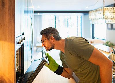 Man cooking, opening oven door in kitchen - p1023m2196679 by Paul Bradbury