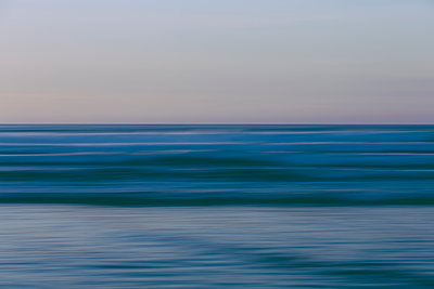 Ocean waves and the view to the horizon over the sea at dusk from the beach.  - p1100m1216308 by Mint Images