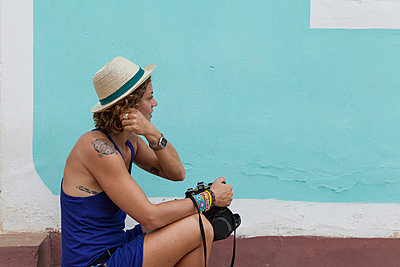 Western girl with vintage camera sitting in the streets of Trinidad - p1166m2087977 by Cavan Images